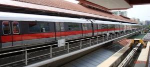 Kereta MRT (Mass Rapid Transport) pada gambar - mengambil penumpang yang diantarkan oleh kereta tunggal LRT (Light Rapid Transit)