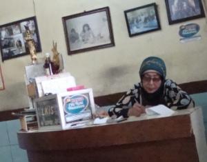 Pemilik sate Bu Yanti - Duren Tiga dengan latar belakang foto hitam putih penyanyi Iwan Fals masih Gondrong dan Kurus